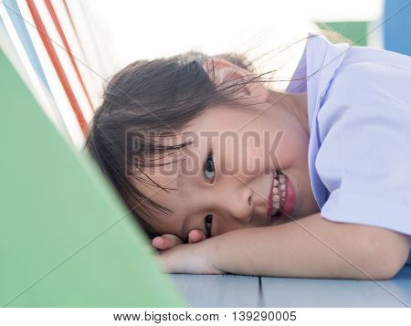Portrait of Asian happy little girl fall down on the table.