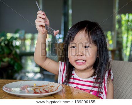 Little Asian girl child eating american breakfast