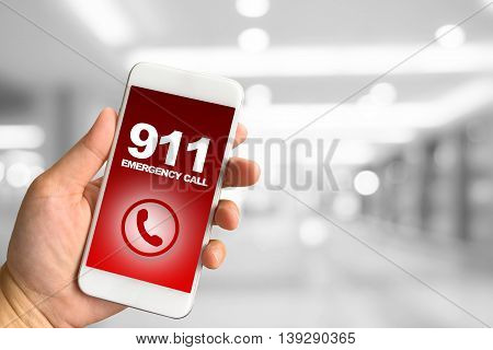 Woman hand holding smartphone against blur bokeh of building background 911 Emergency concept
