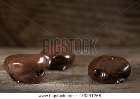 Plums in chocolate on rustic wooden background