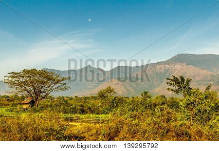 The moon is out over a huge plateau and the green foliage of the Laos countryside