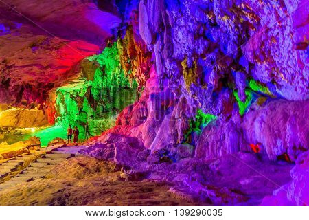 Tourist visit a cave lit up with colorful lights in Laos