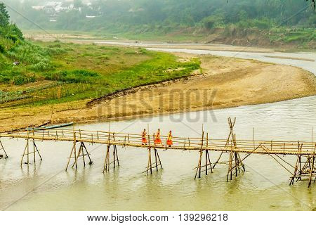 Orange robed buddhist monks walk over a bamboo bridge in Luang Prabang, Laos