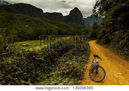 A mountain bike on a dirt road past green fields and mountains on a stormy day in Laos