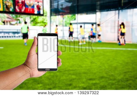 hand of man hold mobile phone over blurred athlete are playing footbal or Soccerl on artificial yard
