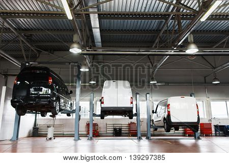 Interior of car repair station, cars on maintenance lifted up on elevators
