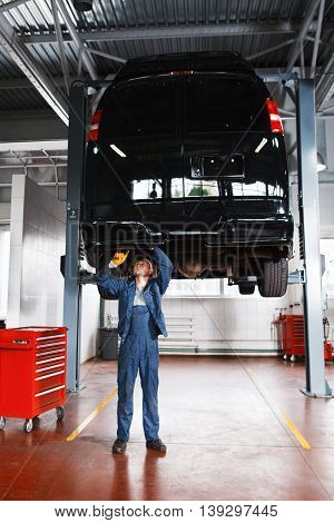 Mechanic working with car suspension system. Automobile on maintenance at service