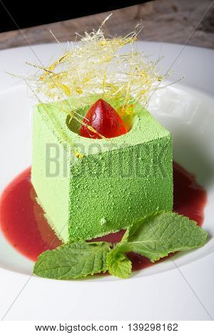 Pistachio green cream mousse dessert served on a white plate