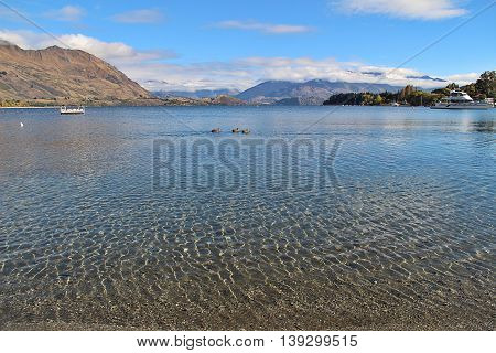 Clear water at lake Wanaka. Background with blue sky and white cloud above mountains