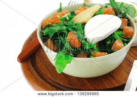 green salad with smoked salmon in green bowl on plate