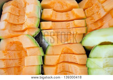 Sliced melon in pieces arranged on steel tray (Other names are cantelope cantaloup honeydew Crenshaw casaba Persian melon and Santa Claus or Christmas melon)