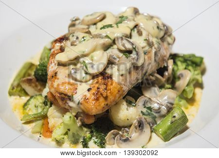 Grilled chicken breast and vegetables served with creamy mushroom sauce