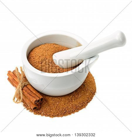 powder and cinnamon sticks mortar with pestle isolated on white background