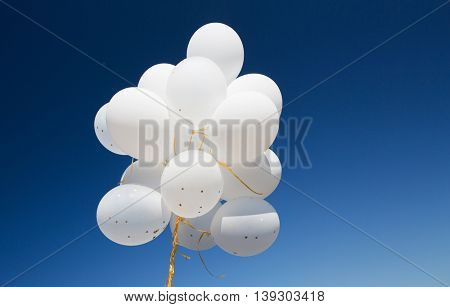 holidays, birthday, party and decoration concept - close up of inflated white helium balloons in blue sky