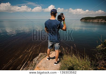 photographer man from behind taking photo, photographing lake