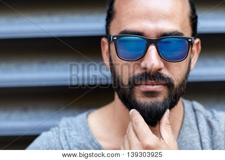 lifestyle, emotion, expression and people concept - man in sunglasses touching beard on city street