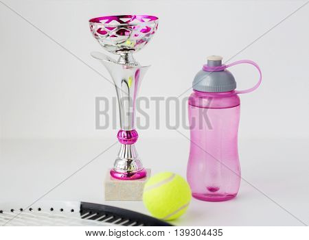 sport, achievement, championship, competition and success concept - close up of tennis racket and ball with cup and bottle over white background