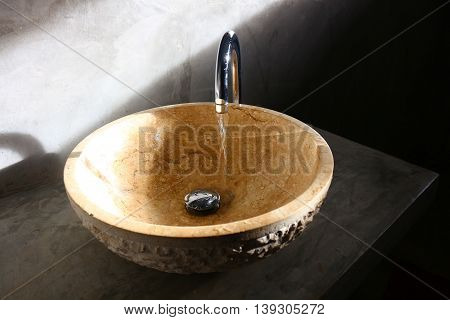 Stone-like washing basin with water tap openning