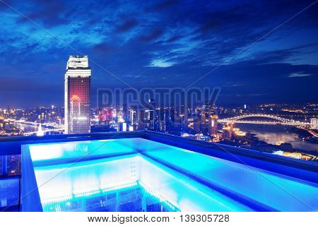 modern office building in downtown of chongqing at twilight on view from abstract glass patio
