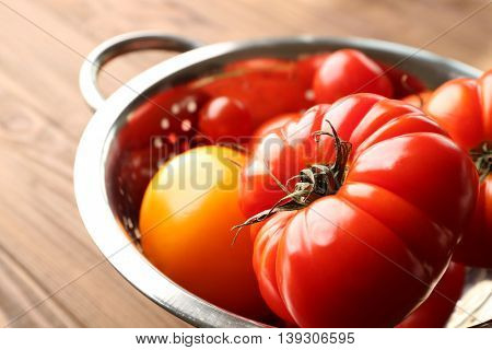 Different tomatoes in colander, close up