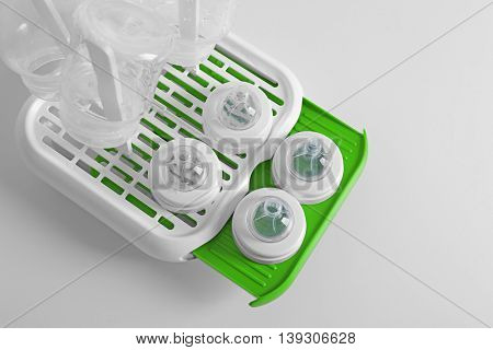 Baby bottles on plastic drying rack on white background