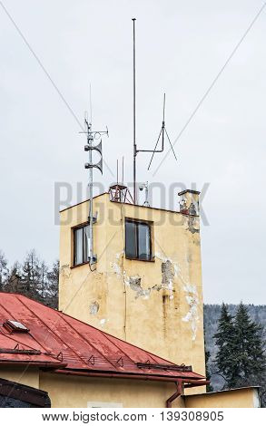 Detail photo of old house with megaphones and antenna. Architectural theme. Vertical composition. Damaged plaster.