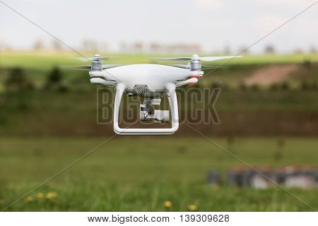White drone quadrocopter with photo camera flying in the blue sky. Concept