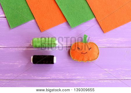 Little orange felt pumpkin, green and black thread, needle, felt sheets on lilac wooden background. Easy at home sewing project for Halloween. Small Halloween decoration. Crafts for kids
