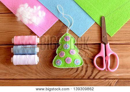 Homemade felt Christmas tree decor. Christmas tree ornament. Hand crafts idea for kids. Thread set, hollofayber, scissors on a wooden table. Top view. Tutorial