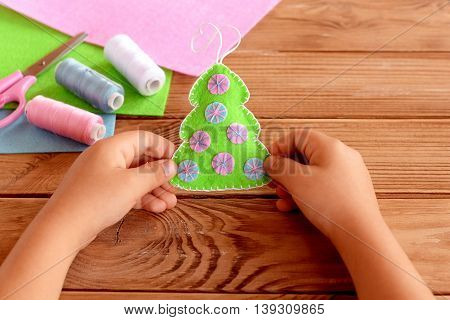 Child holds a felt Christmas tree in his hands. Green felt fur tree decorated with pink and blue balls. Christmas crafts project for kids. Felt sheets, scissors, thread on wooden background