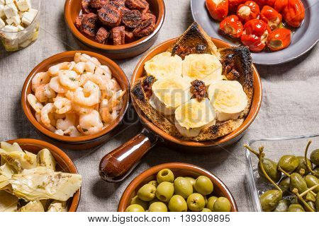 Tapas food served in small bowls cold meat goat cheese. A meal for sharing