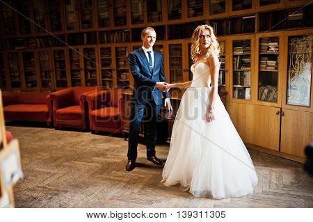 Elegant wedding couple at old vintage library