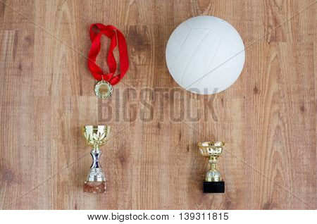 sport, achievement, championship, competition and success concept - close up of volleyball ball with golden medal and cup over wooden background