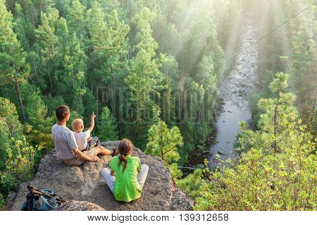 Hikers with backpack sit on big rock above green forest and river