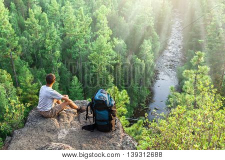 Hiker with backpack sits on big rock above green forest and river