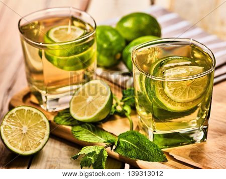 Country alcohol cocktail. On wooden boards are two glasses with green transparent drink and half lime . A drink number one hundred eighty six mojito with mint leaf . Country life. Boards background.