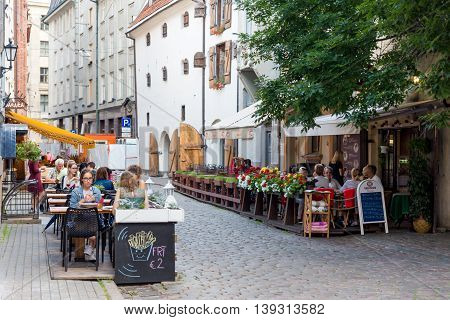 RIGA LATVIA - 16 JULY: View on Riga downtown with tourists in cafe. July 16 2016