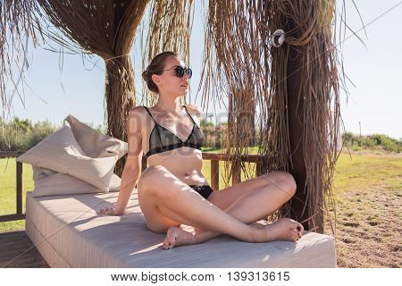 Beautiful young girl in bungalow with sunglasses and black swimsuit having sunbath