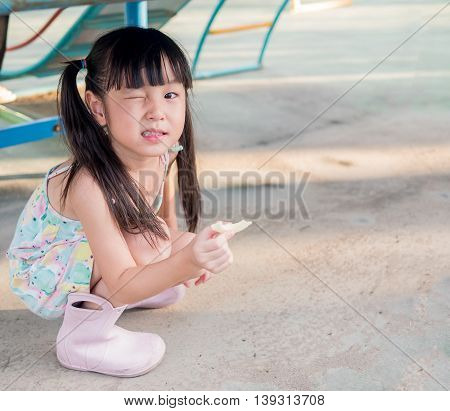asian baby child playing on playground close one eye