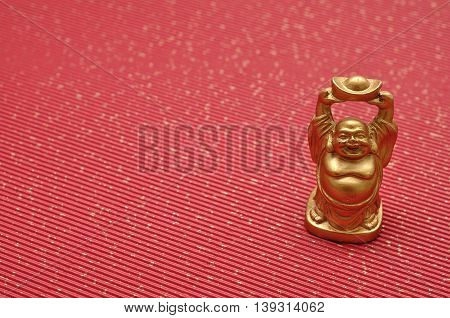 Figurine of laughing and cheerful golden Buddha
