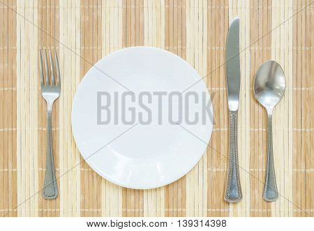 Closeup white ceramic dish with stainless fork and spoon and knife on wood mat textured background on dining table in top view