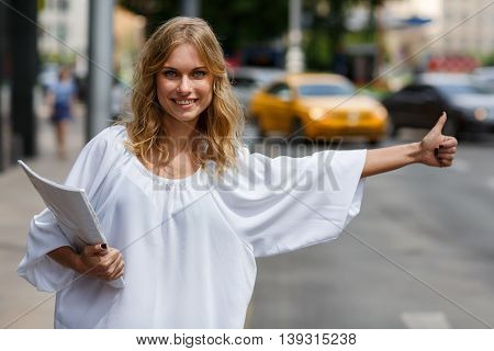 Portrait of smiling young business woman with documents and thumbs up