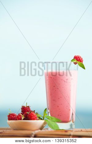 Raspberry milkshake with mint in glass standing on wooden table with sea on the background. Healthe drink in summer, fresh berry drink.