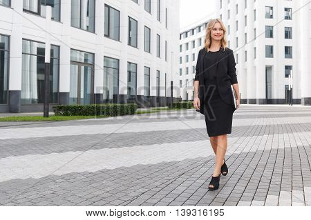 Portrait of confident young business lady with notebook on white modern office building background
