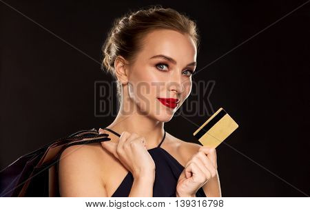 people, luxury and sale concept - beautiful woman with credit card and shopping bags over black background