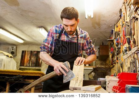profession, carpentry, woodwork and people concept - carpenter with ax and wood plank working at workshop