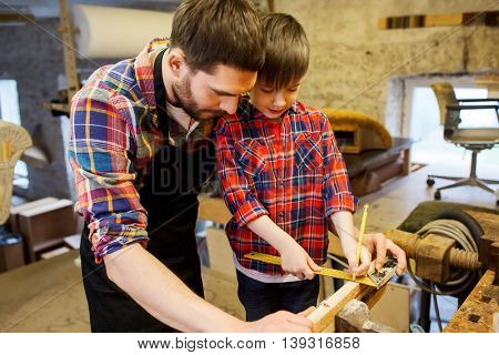 family, carpentry, woodwork and people concept - father and little son with ruler and pencil measuring wood plank at workshop