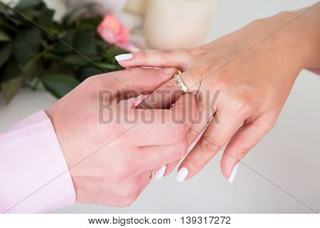 Hands with rings Groom putting golden ring on bride's finger during wedding ceremony Loving couple close-up. In the background flowers.