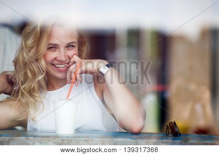 Funny beautiful young blond woman in cafe. Portrait closeup of model flirting and looking in camera