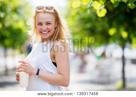 Blond girl walking in park with fresh drink in hot summer day